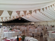 Limewashed bamboo chairs and pumpkins on the tables completed the look in this wedding marquee at West Hill School in Titchfield.